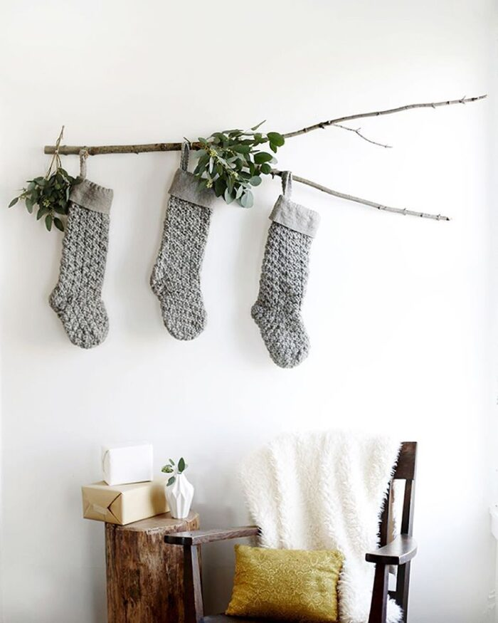 Christmas stockings hanging from a branch -when you don't have a mantel