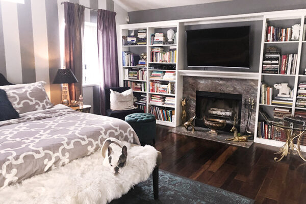 grey and white bedroom with striped accent wall and fireplace and built-in bookshelves