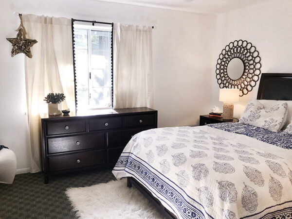 blue and white guest room with dark wood furniture