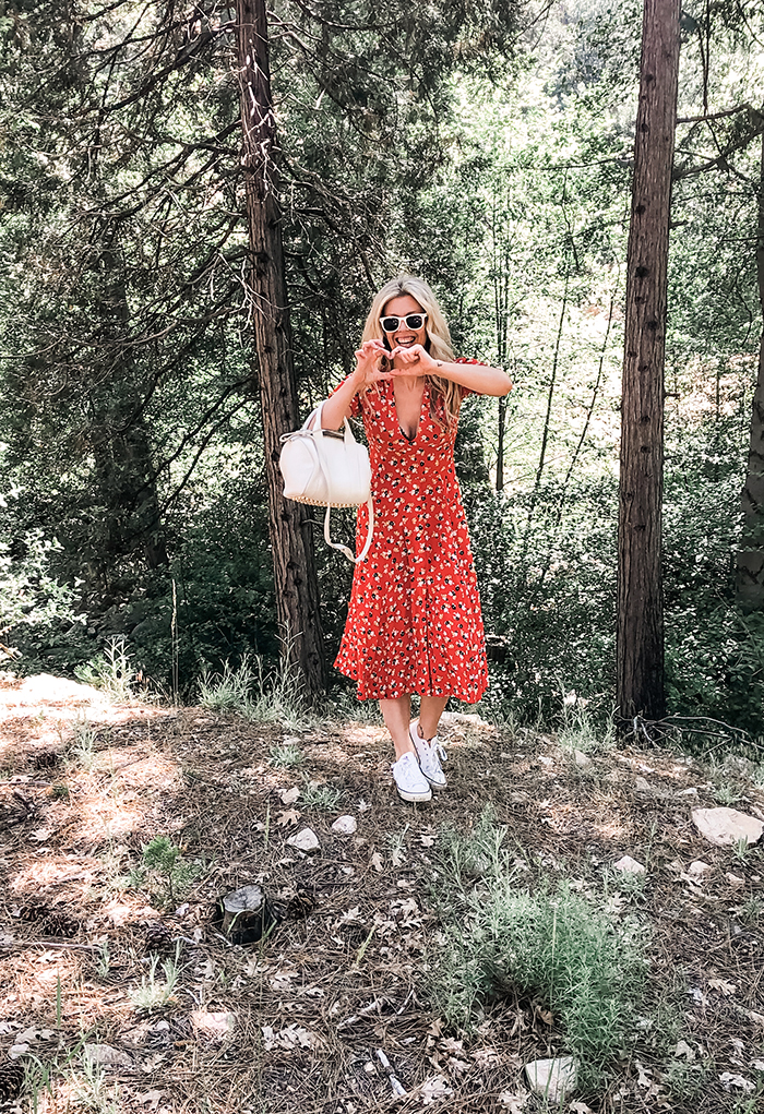 red floral dress with sneakers in the forest