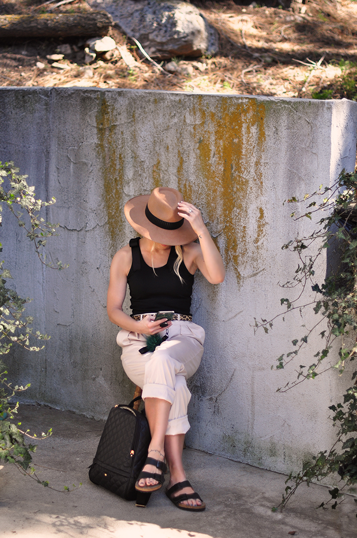 casual spring summer style, loose fitting khaki pants, birkenstocks, wide brim hat and black ribbed tank with shoulder detailing, retro vintage sunglasses, quilted backpack