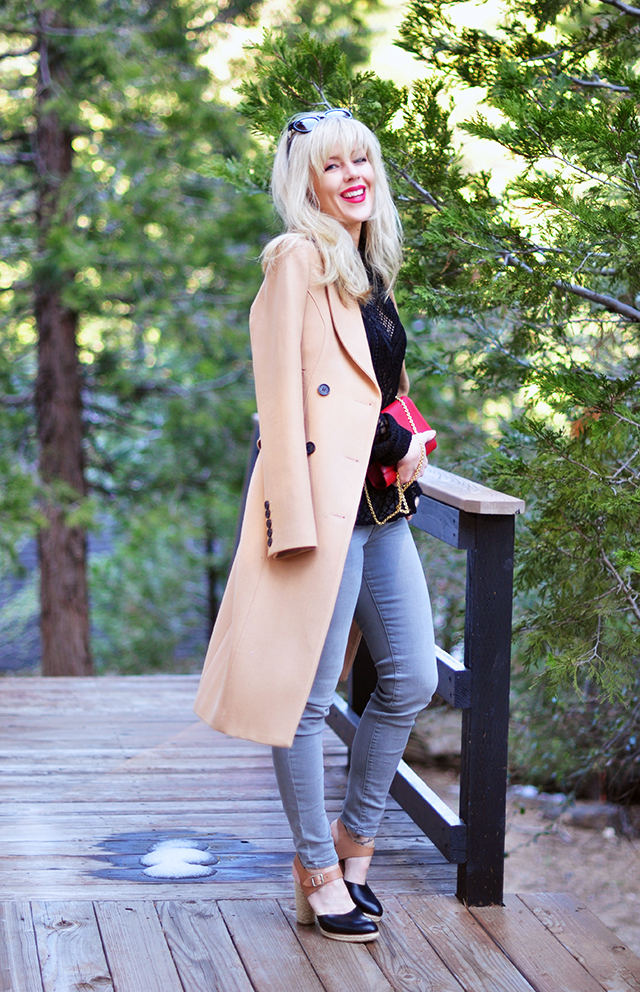 grey jeans lace peplum top and camel coat with red lips and bangs