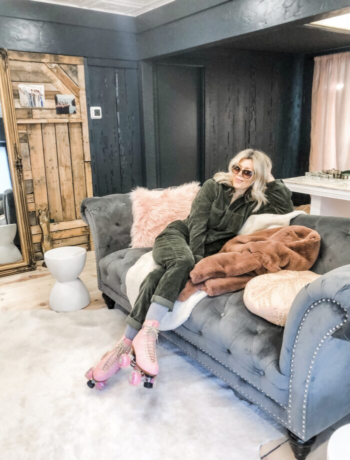 sitting on a couch, grey tufted sofa, corduroy coveralls jumpsuit, pink roller skates, love maegan's office