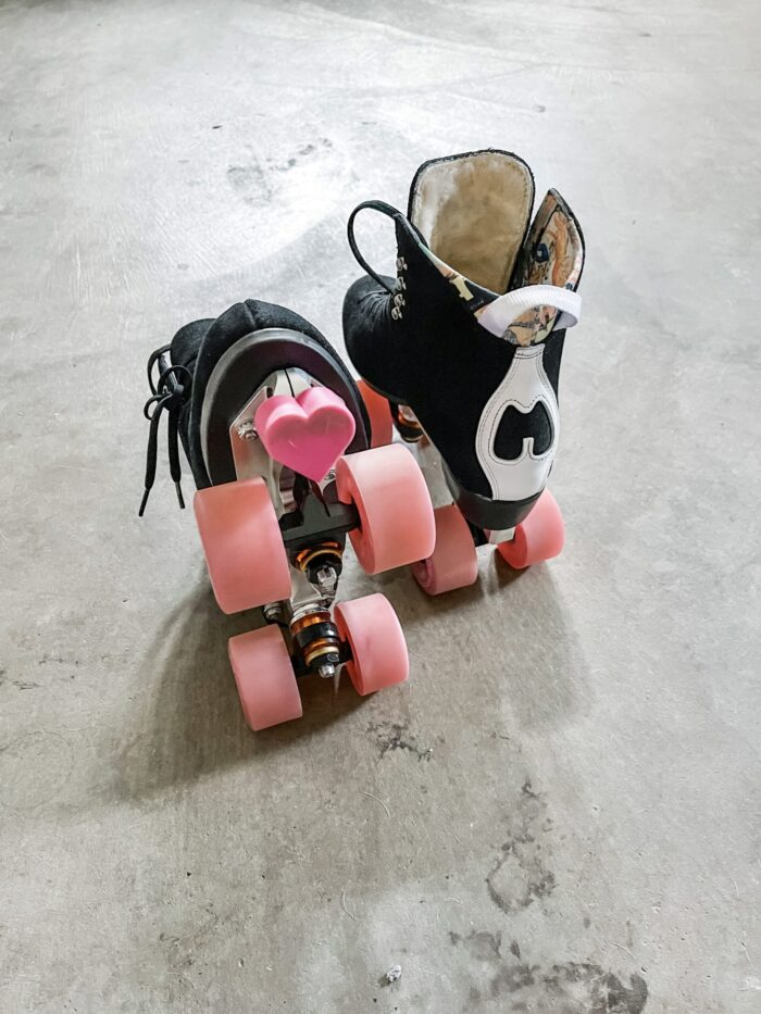 moxi jack boots, moxi skates, roller skates, black skates pink wheels, glow wheels, pink light up roller skate wheels, heart toe stop, pink and black, moxi jack boot skate setup