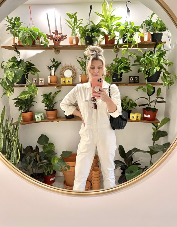 selfie in round mirror with plants in the background, ivory coveralls, lee unionalls, love maegan, blonde messy bun, lake arrowhead, shopping in lake arrowhead, bohemian village boutique
