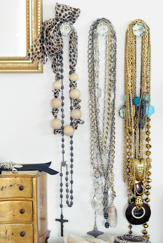 Necklaces hanging from crystal knobs on the wall