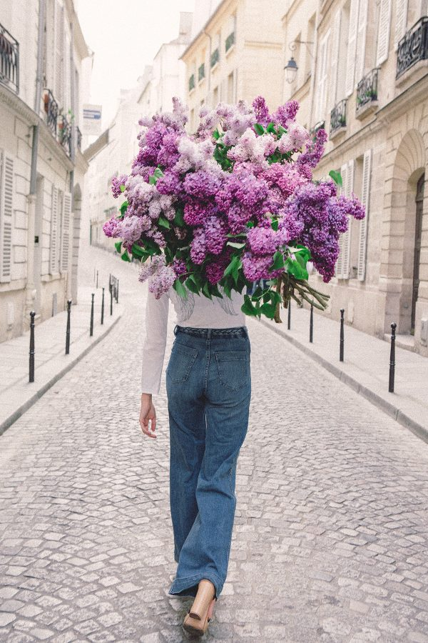 girls carrying flowers over their face