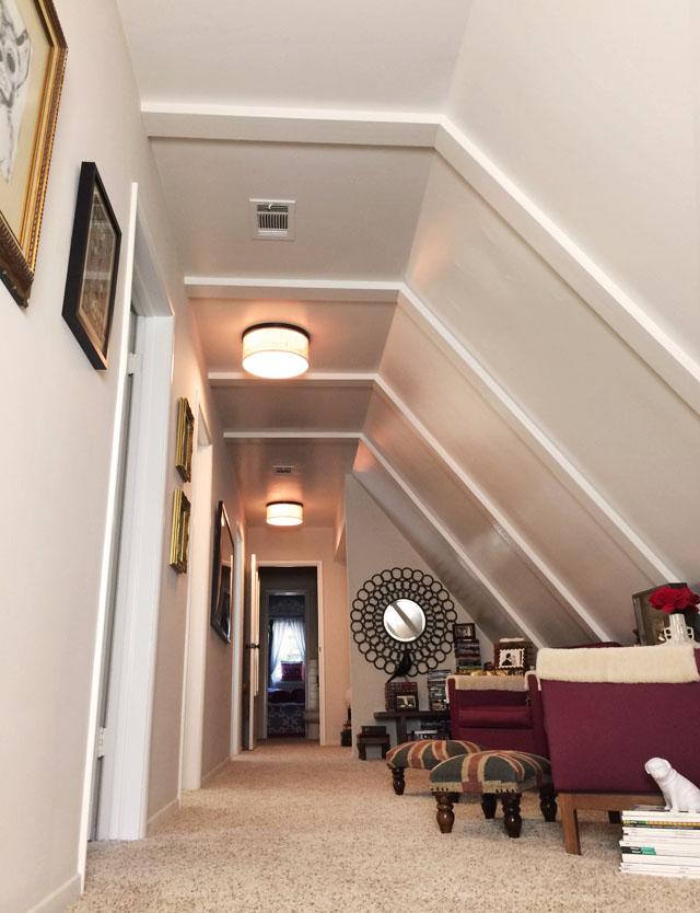 long hallway-slanted ceiling-sitting area